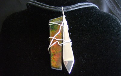 Modern, abstract design, sterling silver & ammolite pendant on cotton cord adaptable to chain or omega. SOLD