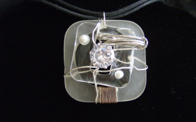 Modern, abstract design, Cubic Zirconia, lucite, pearl pendant on cotton cord adaptable to chain or omega. SOLD